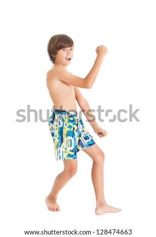 Pretty slender teenage boy wearing swimming shorts, dancing and waving his arms. Studio shot, isolated on white background. - stock photo