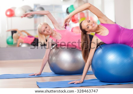 Pretty slim girls are doing exercise in fitness center. They are lying on balls and stretching arm sideways. The ladies are smiling and looking at camera happily - stock photo