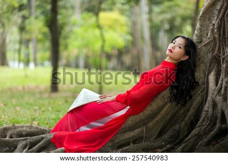 Pretty slim young Vietnamese lady dressed in red traditional clothes relaxing on aerial tree roots in a public park reclining on her back as she stares thoughtfully into the air - stock photo
