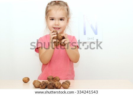 Pretty small girl holding walnuts at the desk with scattered nuts over white background with N letter on it, indoor portrait - stock photo