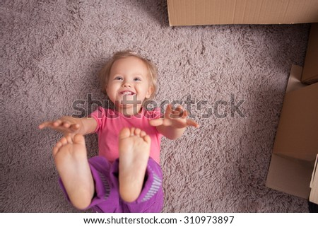 Pretty small girl is lying on flooring with joy. She is stretching her hands and legs up and smiling. There are cardboard boxes near her - stock photo