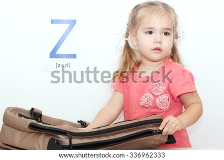 Pretty small girl opening a bag with zipper over white background with Z letter on it, indoor portrait, ABC concept - stock photo