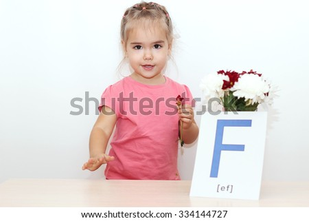 Pretty small girl standing near the bunch of flowers and picture with F letter over white background, indoor portrait - stock photo