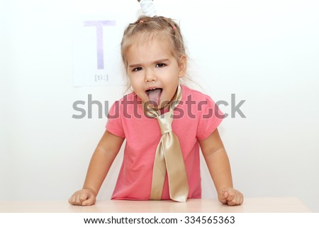 Pretty small girl wearied a tie sticking her tongue out over white background with T letter on it, indoor portrait - stock photo