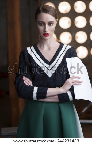 Pretty smart actress wearing sweater holding her scripts. Cross arms. - stock photo