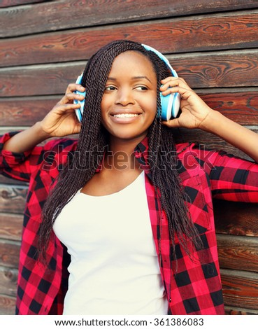 Pretty smiling african woman with headphones enjoying listens to music in city - stock photo