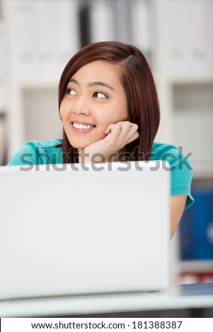 Pretty smiling Asian student sitting thinking with her chin on her hands as she sits behind her laptop staring off to the side daydreaming - stock photo