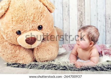pretty smiling baby girl and teddy bear lying on fluffy blanket - stock photo