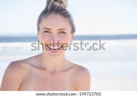 Pretty smiling blonde on the beach on a bright day - stock photo