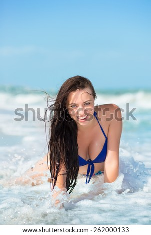 Pretty smiling brunette posing on the beach - stock photo