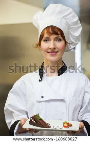 Pretty smiling chef presenting chocolate cake with strawberries on white plate - stock photo