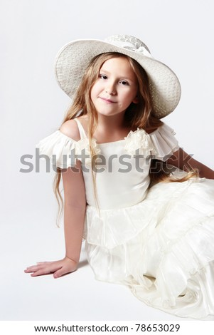 Pretty smiling child girl in white dress and hat. Portrait of elegant sitting girl 10 years old. - stock photo