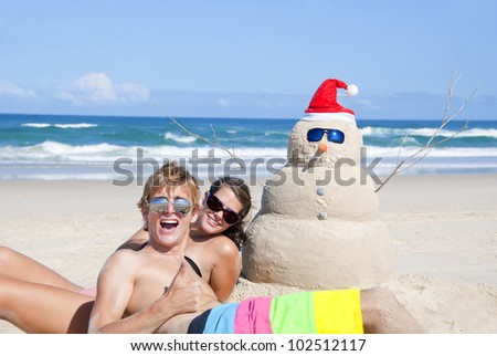 Pretty smiling couple having fun at Australian beach with snowman made out of sand wearing sunglasses at christmas eve. - stock photo
