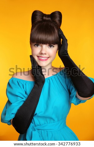 Pretty smiling girl beauty portrait. Elegant Fashion Glamorous teen Model wearing black Glamour Gloves. Bow Hairstyle and Make-up. female  isolated on studio yellow background. - stock photo
