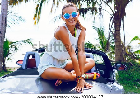 Pretty smiling girl sitting on luxury car, and having fun on vacation, wearing bright summery dress and sunglasses, palm trees background. - stock photo