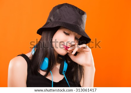Pretty smiling girl, with blue headphones on her neck, wearing in black blouse and cap, posing on orange background, in studio, waist up - stock photo