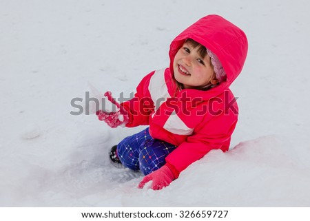 Pretty smiling little girl in winter clothes sitting in snowdrift, holding piece of snow. Walking with kids in cold snowy weather. Concept of healthy well being. - stock photo