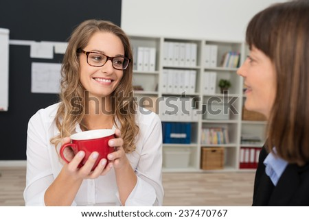 Pretty Smiling Office Girl with Long Wavy Blond Hair Holding Red Cup of Coffee While Talking to Female Co - Worker at the Office. - stock photo