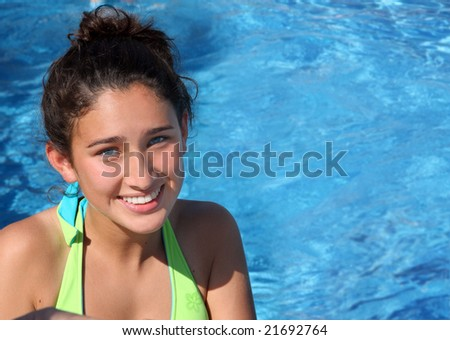Pretty smiling teen girl in a pool - stock photo