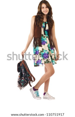 Pretty smiling teenage girl in flowered dress and fringed vest strolls carrying a backpack. Vertical, isolated on white, copy space. - stock photo