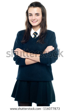 Pretty smiling teenager looking at you confidently. Arms folded - stock photo