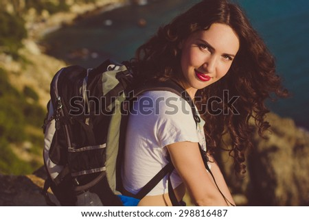 Pretty smiling traveler girl backpacker is drinking water on rock peak over sea view with backpack, summer vacations - stock photo