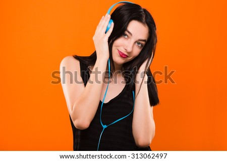 Pretty smiling woman, in black blouse, listening to music with big blue headphones - isolated on orange background, in studio, waist up - stock photo