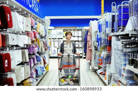 pretty smiling woman pushing cart looking at household items in supermarket - stock photo