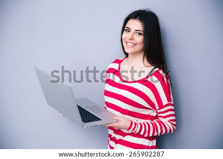Pretty smiling woman standing with laptop over gray background. Looking at camera - stock photo