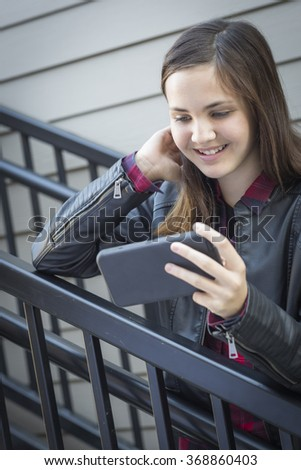 Pretty Smiling Young Girl on Staircase Looking at Smart Phone. - stock photo