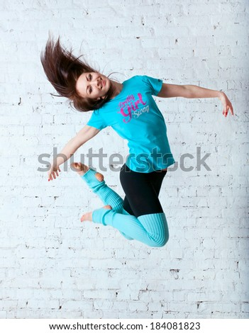 Pretty sporty barefooted woman dancer wearing black leggings, blue t-shirt and gaiters, dancing, jumping up in the air, posing, smiling and looking happily at camera. Over a brick wall background - stock photo