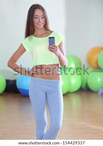 Pretty sporty girl photographing herself in mirror at phone in fitness room - stock photo