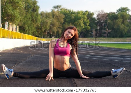Pretty sporty strong slim and fit young woman sitting, doing split and stretching exercises, sitting on a full split. At stadium, on running tracks. During sunset. Green trees at background - stock photo