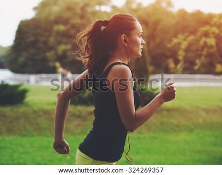 Pretty sporty woman jogging at park in sunrise light - stock photo