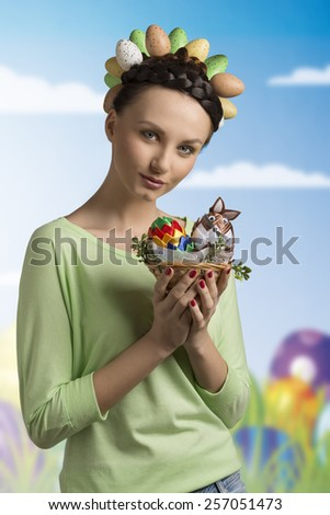Pretty, spring, easter, brunette woman with funny hairstyle with eggs and she is holding little basket with easter decorations. - stock photo
