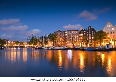 Pretty starry night time illuminations of dutch doll houses reflected in the tranquil canals of Amsterdam. - stock photo