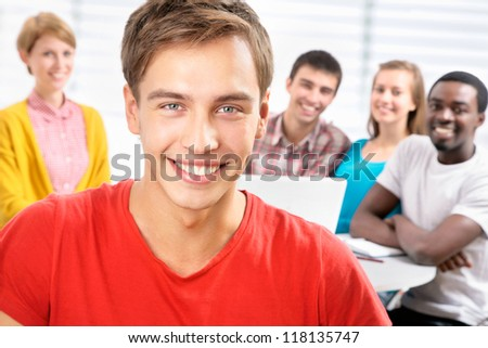 Pretty  student and his friends on background - stock photo