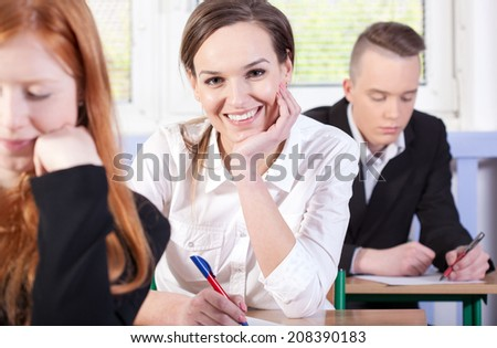 Pretty student during writing an exam, horizontal - stock photo