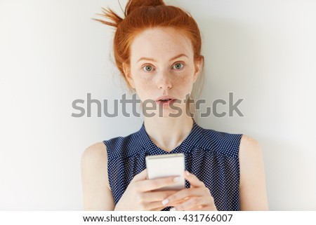 Pretty student girl with ginger hair and freckles holding mobile phone, typing or reading a message, texting online with friends via social networks, looking at the camera with serious expression - stock photo