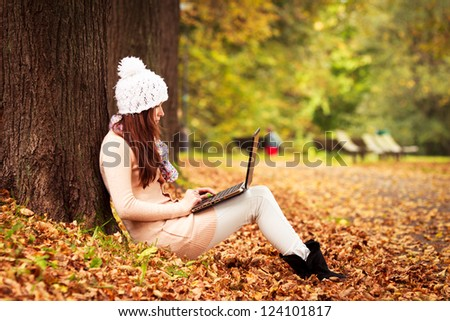 Pretty student girl with laptop in autumn park. Young European Teen Girl. Girl With Laptop. - stock photo