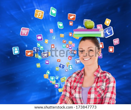 Pretty student holding an apple and books on her head against technological background with hexagons - stock photo
