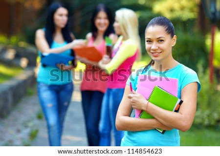 pretty student outdoors with a group of people on the background - stock photo