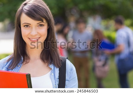 Pretty student smiling at camera outside on campus at the university - stock photo
