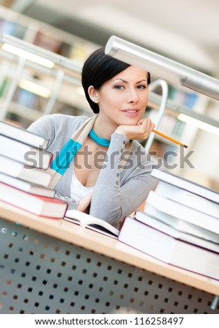 Pretty student studies with piles of books sitting at the table at the reading hall - stock photo