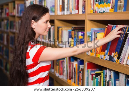 Pretty student taking book from shelf in library at the university - stock photo