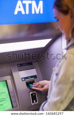 Pretty student withdrawing cash at an ATM - stock photo