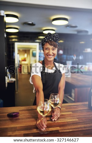 Pretty successful African American businesswoman standing behind the wooden counter in her pub serving glasses of white wine to a customer with a warm friendly smile, small business owner - stock photo