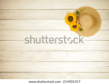 Pretty Sunflowers Picked from garden on ladies sunhat on texture rustic white board background from above with blank or empty room or space for copy, text, your words.  Horizontal, warm sepia tone - stock photo