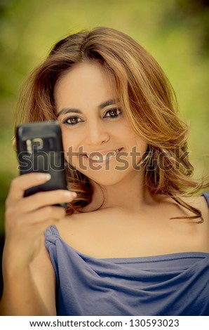 Pretty tanned woman taking picture from mobile camera - stock photo