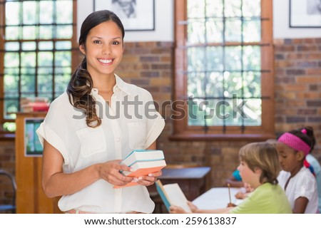 Pretty teacher smiling at camera in library at the elementary school - stock photo